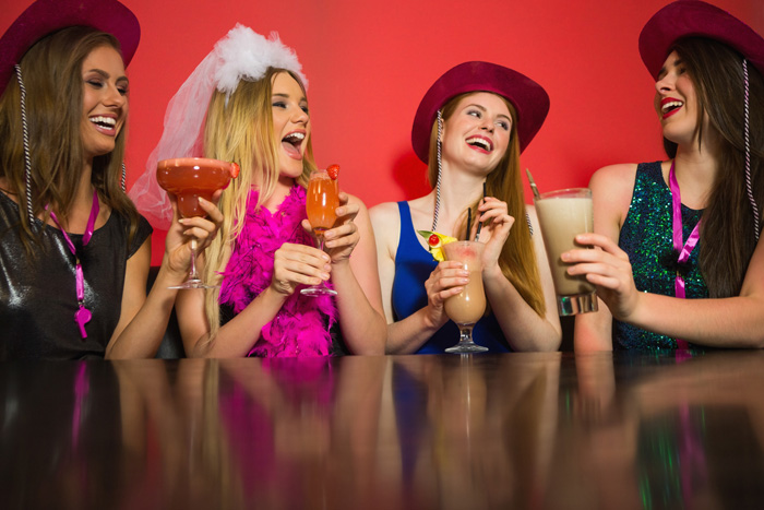 Laughing friends at a hen night drinking cocktails and chatting